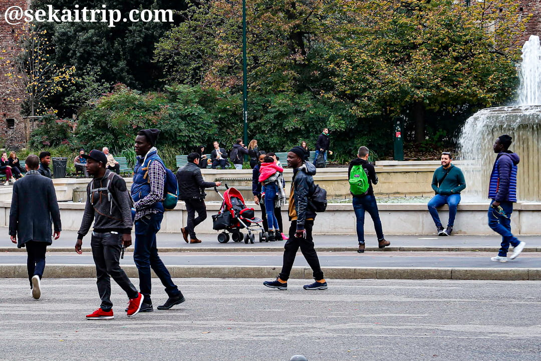 スフォルツェスコ城前にいる黒人のミサンガ売り